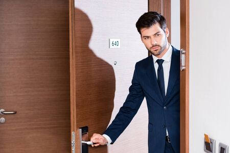 handsome and bearded businessman in suit entering hotel room Stock Photo