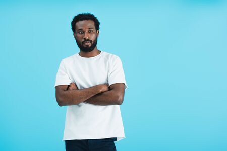 pensive african american man in white t-shirt with crossed arms isolated on blue