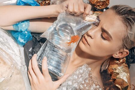 sad wet woman with closed eyes holding goldfish in plastic bag among rubbish in bathtub 版權商用圖片