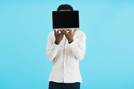 African American man showing laptop with blank screen isolated on blue background Stock Photo