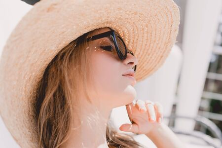Portrait of attractive dreamy blonde woman sunbathing in sunglasses and straw hat