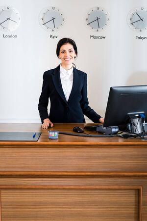 Cheerful brunette receptionist in formal wear standing near computer monitor in hotel