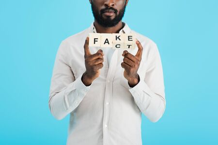 cropped view of african american man holding alphabet blocks with fact word, isolated on blue