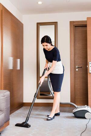 Criada morena limpieza de alfombras con aspiradora en la habitación del hotel