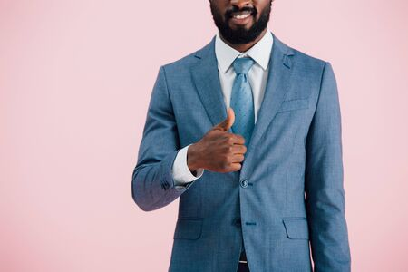 cropped view of african american businessman in suit showing thumb up, isolated on pink