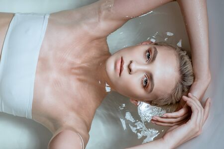 Top view of sexy woman lying in clear water in bathtub 写真素材