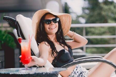 Happy beautiful brunette young woman in swimsuit, straw hat and sunglasses sunbathing near strawberry cocktail