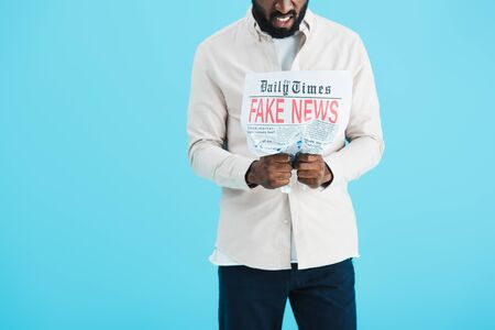 Cropped view of angry African American man reading newspaper with fake news isolated on blue background Stock Photo