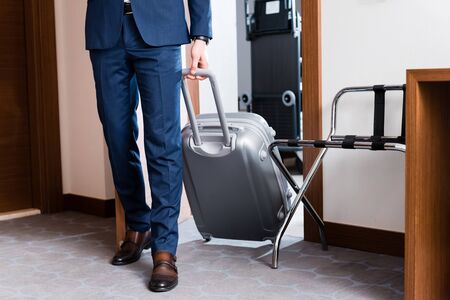 Cropped view of man in formal wear entering hotel room with luggage