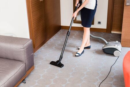 Cropped view of housemaid cleaning carpet with vacuum cleaner Foto de archivo - 126295178