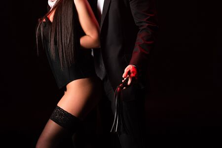 Partial view of bdsm couple with flogging whip isolated on black background
