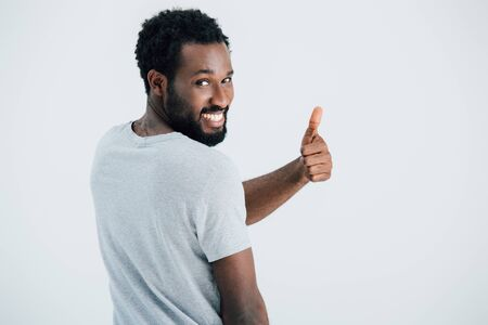 Happy African American man in grey t-shirt showing thumb up isolated on grey background