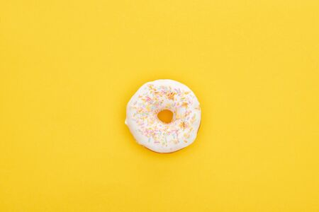 Top view of tasty white glazed doughnut with sprinkles on bright yellow background
