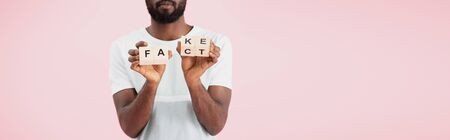 Cropped view of African American man holding alphabet blocks with fact word, isolated on pink background