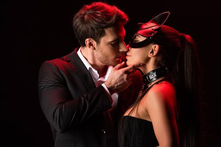 Man in formal wear kissing bdsm girl isolated on black background