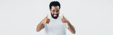 Cheerful African American man in grey t-shirt showing thumbs up isolated on grey background