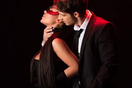 Hombre en ropa formal tocando chica sensual en máscara aislada sobre fondo negro Foto de archivo
