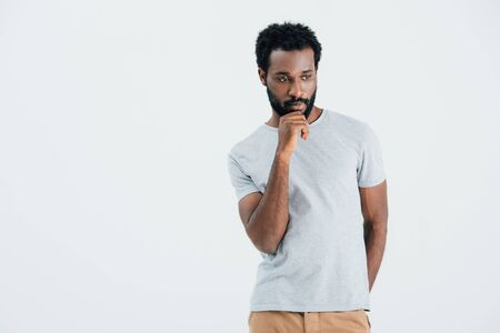 Thoughtful African American man in grey t-shirt, isolated on grey background