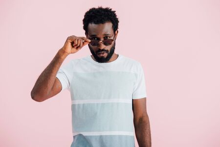 Handsome young African American of man in sunglasses isolated on pink background Stock Photo