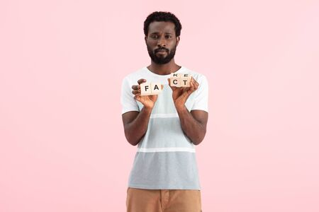 African American man holding alphabet cubes with fact word, isolated on pink background