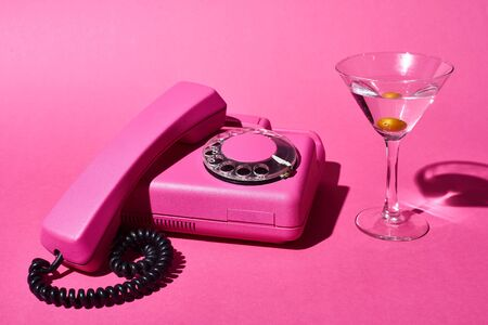 Cocktail with olive and retro bright pink telephone on pink background Фото со стока - 126295528