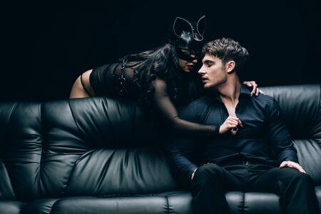 Femme sexy en costume déshabillant son petit ami sur un canapé en cuir noir isolé sur fond noir