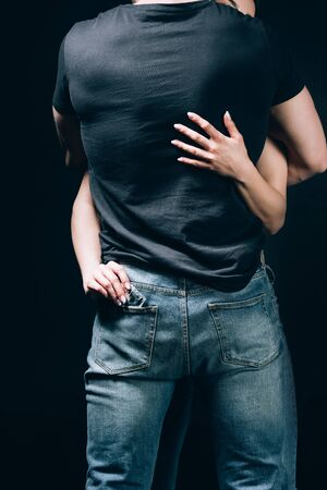 Back view of woman hugging man in jeans and taking out condom from pocket isolated on black background Imagens
