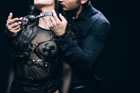 Cropped view of handsome young man holding gag near sexy woman in bdsm costume isolated on black background Imagens