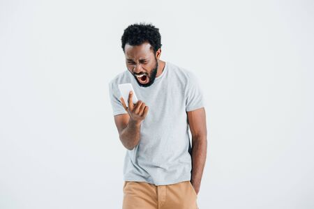 Aggressive African American man shouting and using smartphone, isolated on grey background Imagens
