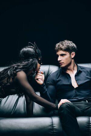 Femme brune sexy en costume tentant homme passionné sur canapé en cuir noir isolé sur fond noir