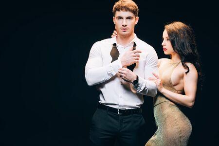 Sexy elegante junge Frau, die hübschen Freund auf schwarzem Hintergrund isoliert anschaut Standard-Bild