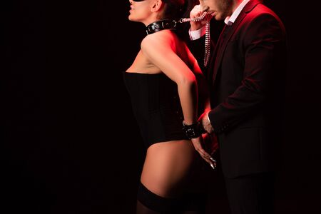 Cropped view of sexy bdsm couple with handcuffs isolated on black background