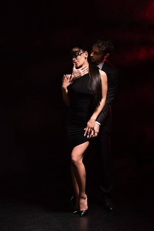 Full length view of bdsm couple embracing on black background 写真素材