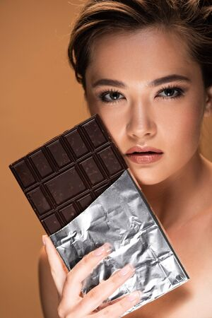 Young naked woman holding chocolate bar in silver foil near face isolated on beige background