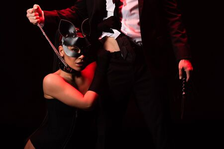 Cropped view of man in formal wear holding flogging whip and bdsm girl in mask and collar isolated in black background