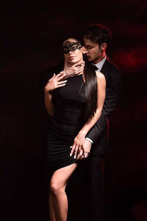 Uomo in abbigliamento formale che abbraccia la fidanzata in abito e maschera su sfondo nero Archivio Fotografico
