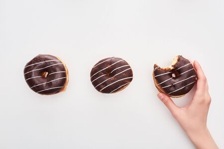 Partial view of woman holding glazed chocolate bitten doughnut on white background 写真素材
