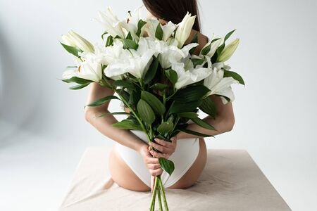 Back view of tender young woman holding bouquet of lilies behind back on white background