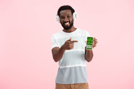 African American man listening music with headphones and pointing at smartphone with health app, isolated on pink background Standard-Bild