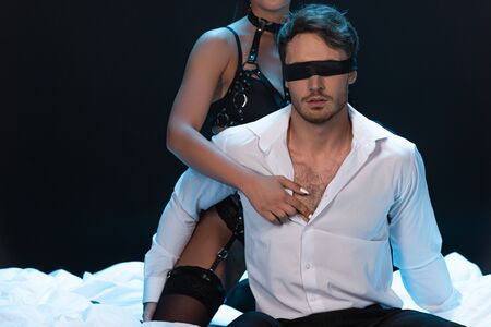 Cropped view of bdsm girl with blindfolded boyfriend on bed isolated on black background