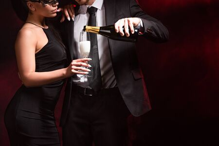 Cropped view of man in formal wear pouring champagne to woman in dress and mask on black background Foto de archivo