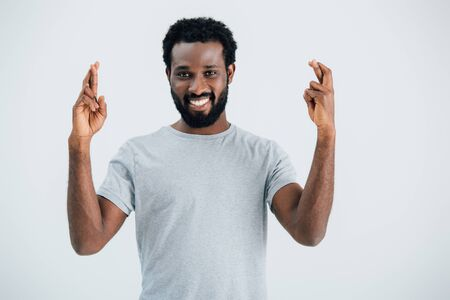 Smiling African American man with crossed fingers isolated on grey background Banque d'images - 126296101