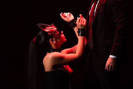 Cropped view of man in formal wear and girl in mask and handcuffs isolated on black background