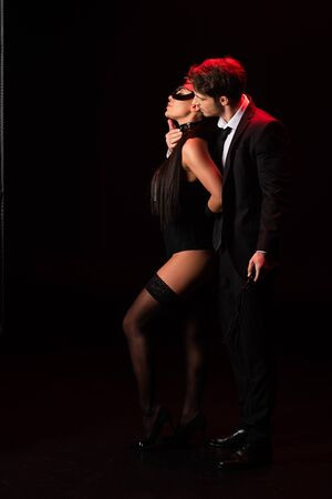 Full length view of couple embracing on black background