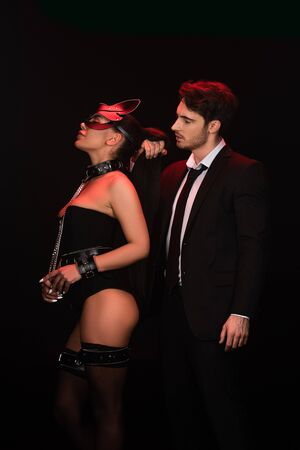 Man in formal wear with bdsm woman in collar isolated on black background