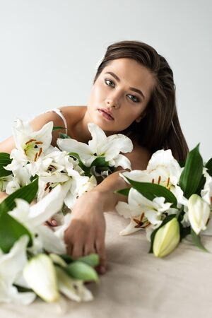 Tender young woman looking at camera among lilies isolated on white background Stock Photo