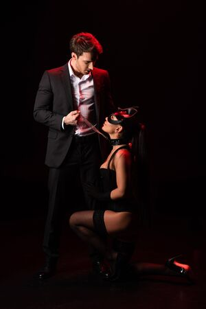 Full length view of bdsm couple looking at each other on black background
