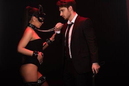 Couple sexy avec des menottes isolé sur fond noir Banque d'images