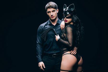 Junger Mann in der Nähe einer Frau im Kostüm mit Peitschenpeitsche auf schwarzem Hintergrund isoliert Standard-Bild