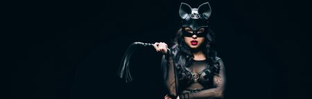 Panoramic shot of sexy young brunette woman in bdsm costume and mask with leather flogging whip isolated on black background